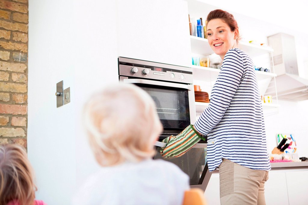 Mother wearing oven gloves opening oven : Stock Photo