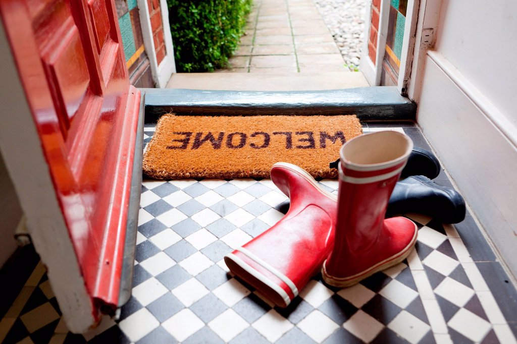 Welcome mat and wellington boots : Stock Photo