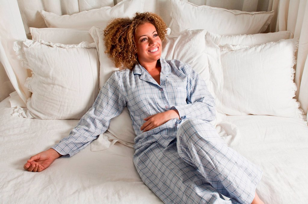 Stock Photo: 1439R-1148815 Woman wearing pyjamas reclining in bed