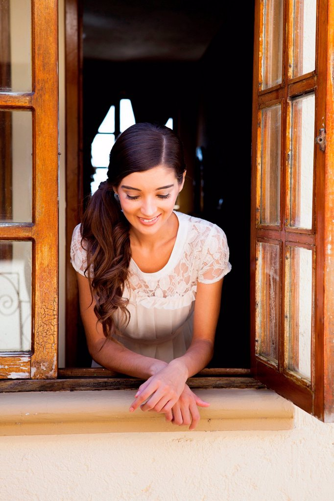 Stock Photo: 1439R-1148866 Young woman looking out of window