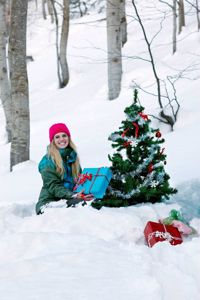 Stock Photo: 1439R-1148915 Woman sitting by christmas tree with gift