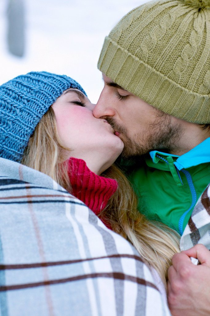 Stock Photo: 1439R-1148922 Couple wrapped in blanket, kissing