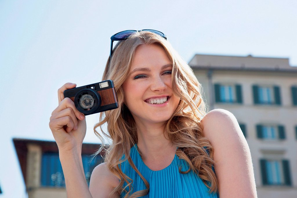 Stock Photo: 1439R-1148936 Young woman holding vintage camera