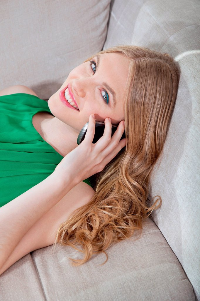 Stock Photo: 1439R-1148947 Young woman on cellphone, lying on sofa