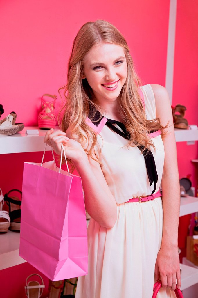 Stock Photo: 1439R-1148972 Happy young woman in shoe store with shopping bag