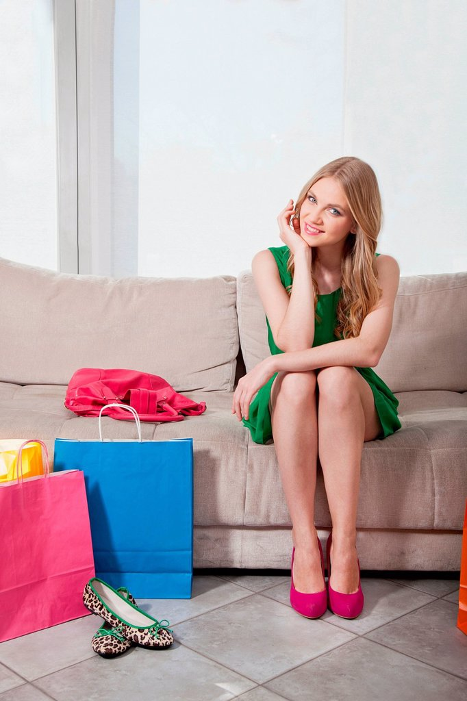 Stock Photo: 1439R-1148973 Young woman sitting on sofa with shopping bags
