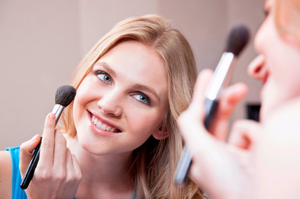 Stock Photo: 1439R-1148978 Young woman applying blusher in the mirror