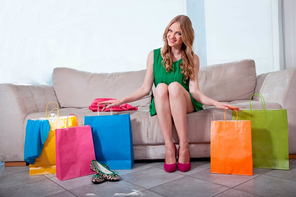 Young woman sitting on sofa with shopping bags : Stock Photo