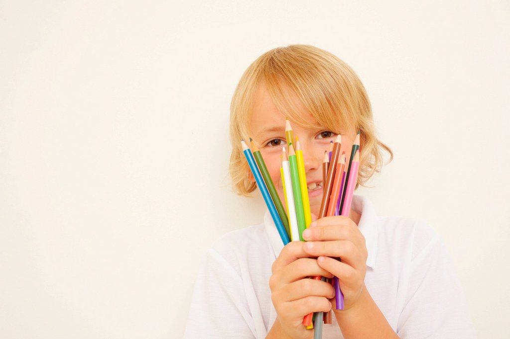 Stock Photo: 1439R-1149034 Schoolboy holding bunch of colouring pencils