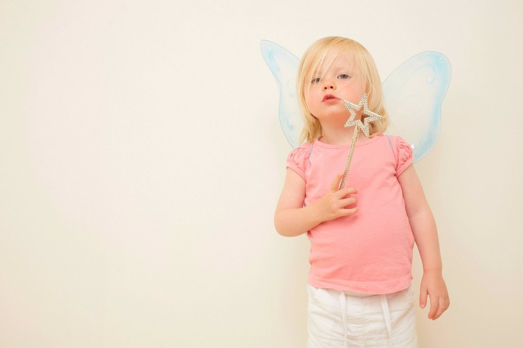Toddler wearing wings, holding wand : Stock Photo