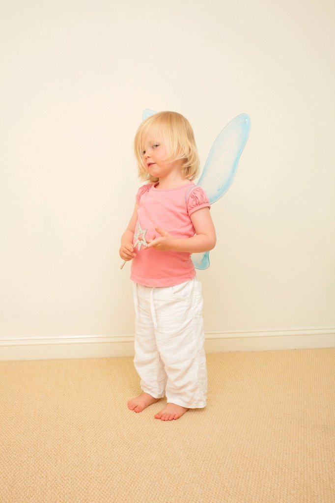 Stock Photo: 1439R-1149045 Toddler wearing wings, holding wand
