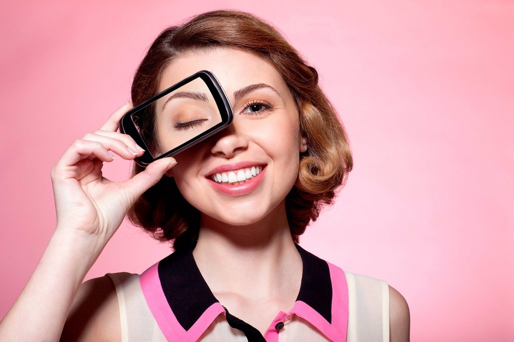 Stock Photo: 1439R-1149065 Woman with smartphone over eye