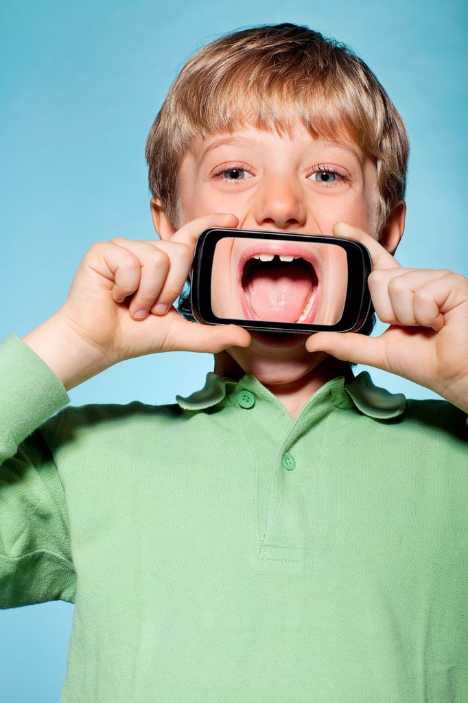 Stock Photo: 1439R-1149120 Boy holding smartphone over mouth