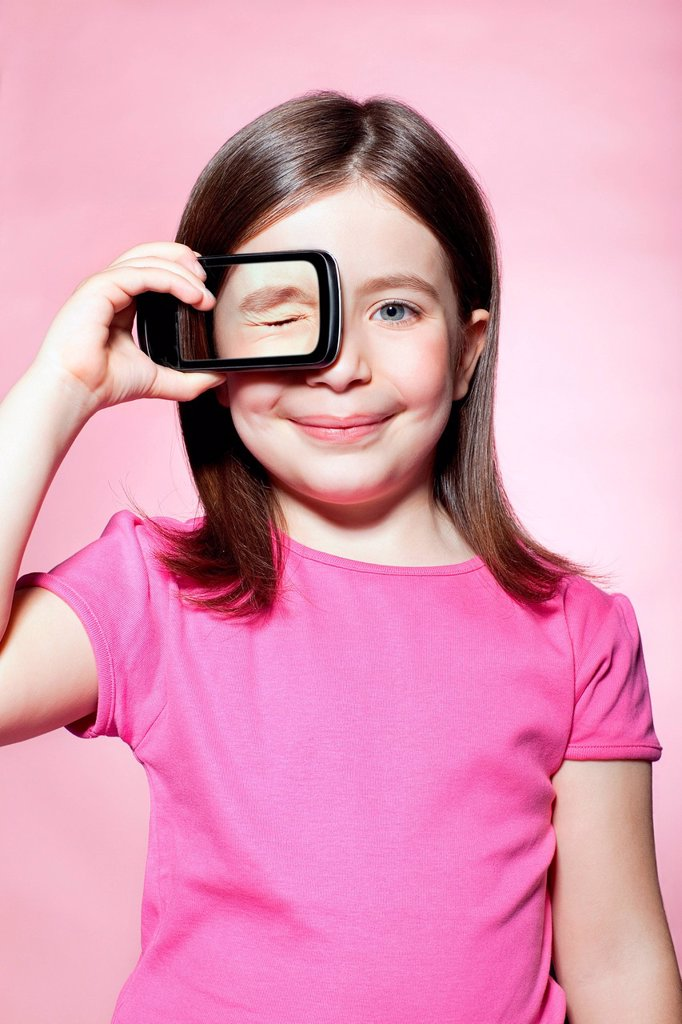 Stock Photo: 1439R-1149123 Girl holding smartphone over eye
