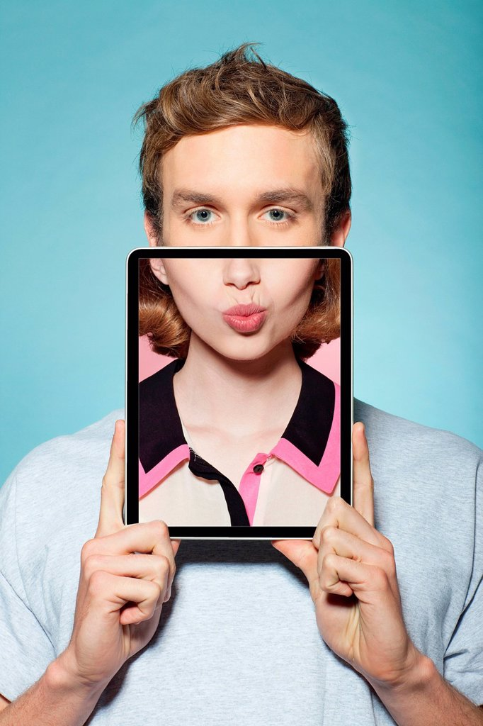 Stock Photo: 1439R-1149129 Man covering half his face with digital tablet, with womans mouth