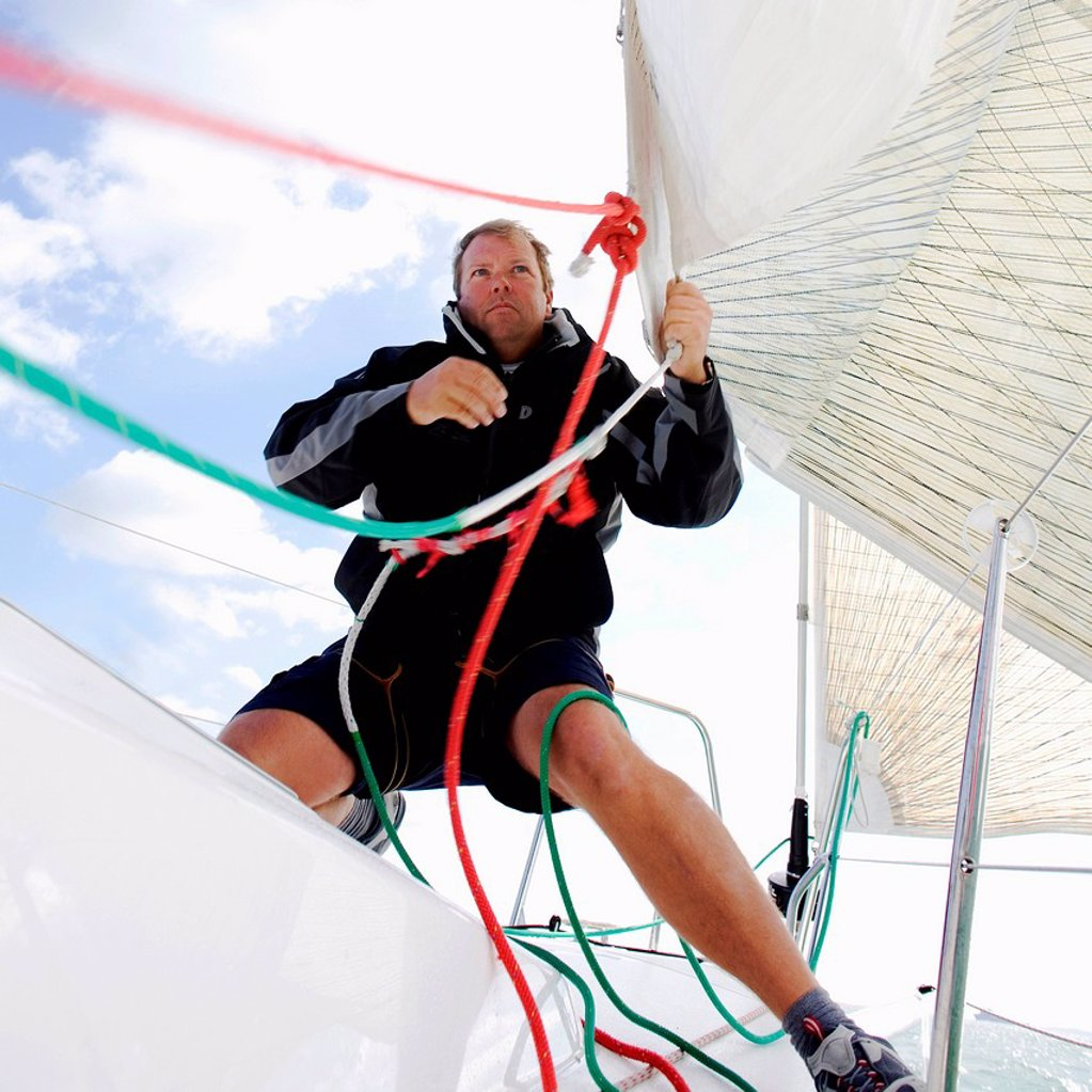 Man on yacht, pulling ropes : Stock Photo