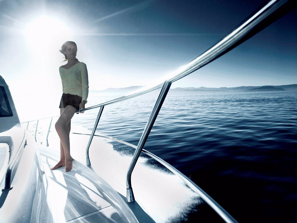 Stock Photo: 1439R-1149149 Woman standing on deck of yacht