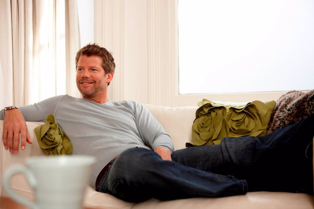 Man relaxing on sofa : Stock Photo