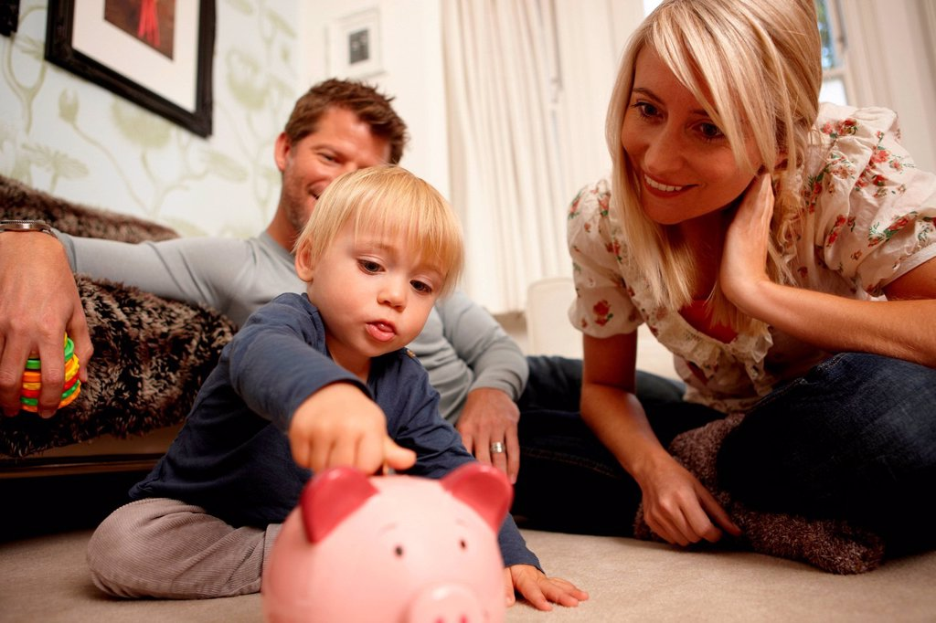 Father, mother and son putting coins in piggy bank : Stock Photo