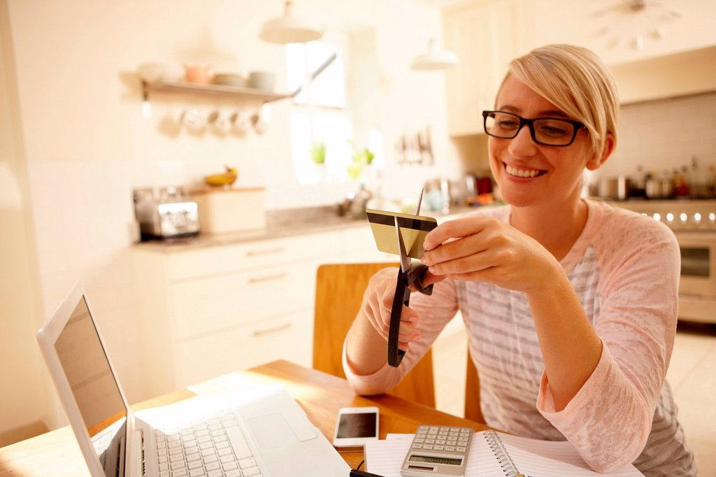 Stock Photo: 1439R-1149237 Woman cutting credit card with scissors