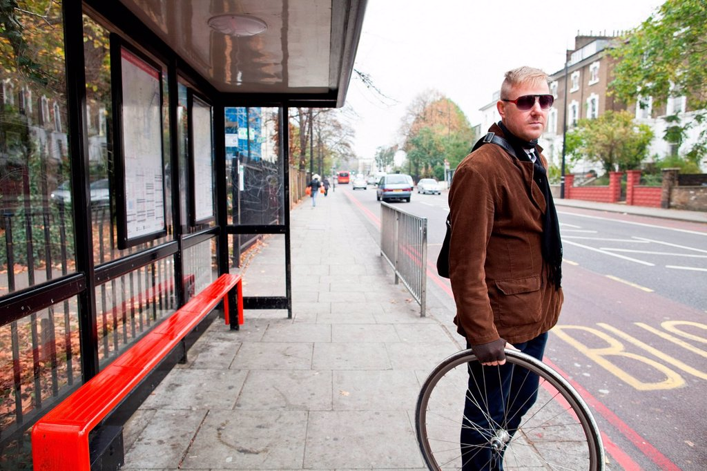 Stock Photo: 1439R-1149393 Cyclist waiting at bus stop