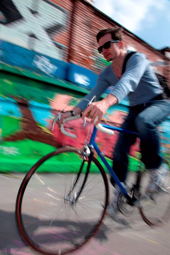 Stock Photo: 1439R-1149466 Mid adult cyclist riding passed graffiti