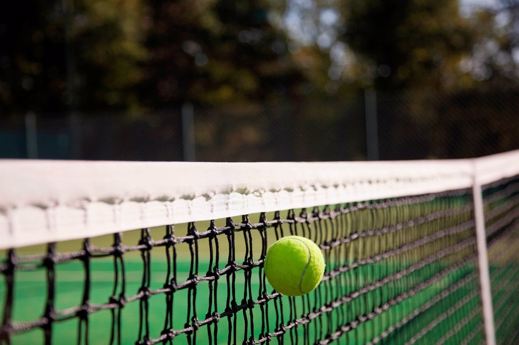 Tennis ball hitting net : Stock Photo