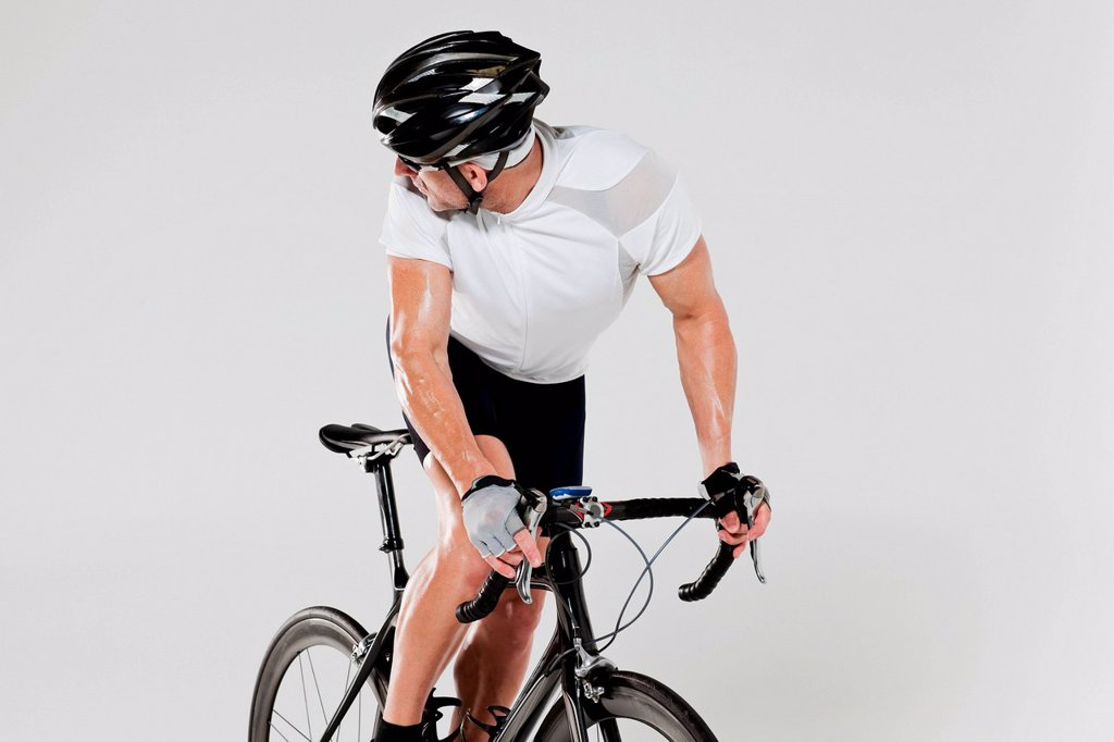 Stock Photo: 1439R-1149573 Male cyclist looking over shoulder