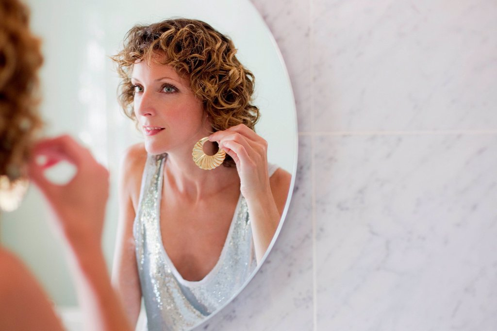 Mid adult woman putting on earrings in mirror : Stock Photo