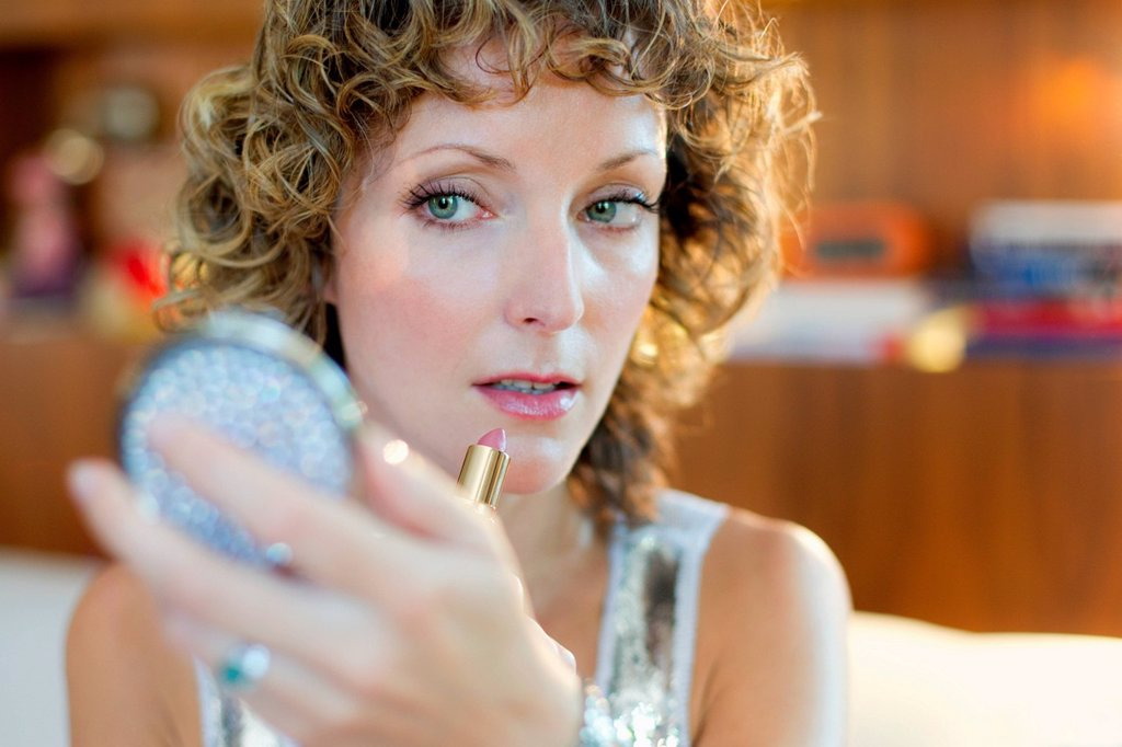 Stock Photo: 1439R-1149581 Mid adult woman applying lipstick