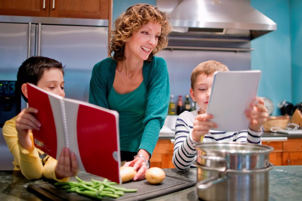 Mid adult woman cooking in kitchen with sons : Stock Photo