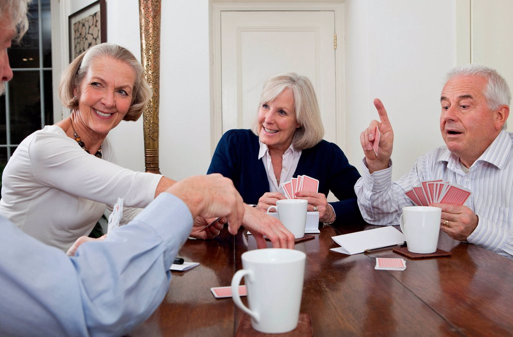 Stock Photo: 1439R-1149663 Senior friends playing cards