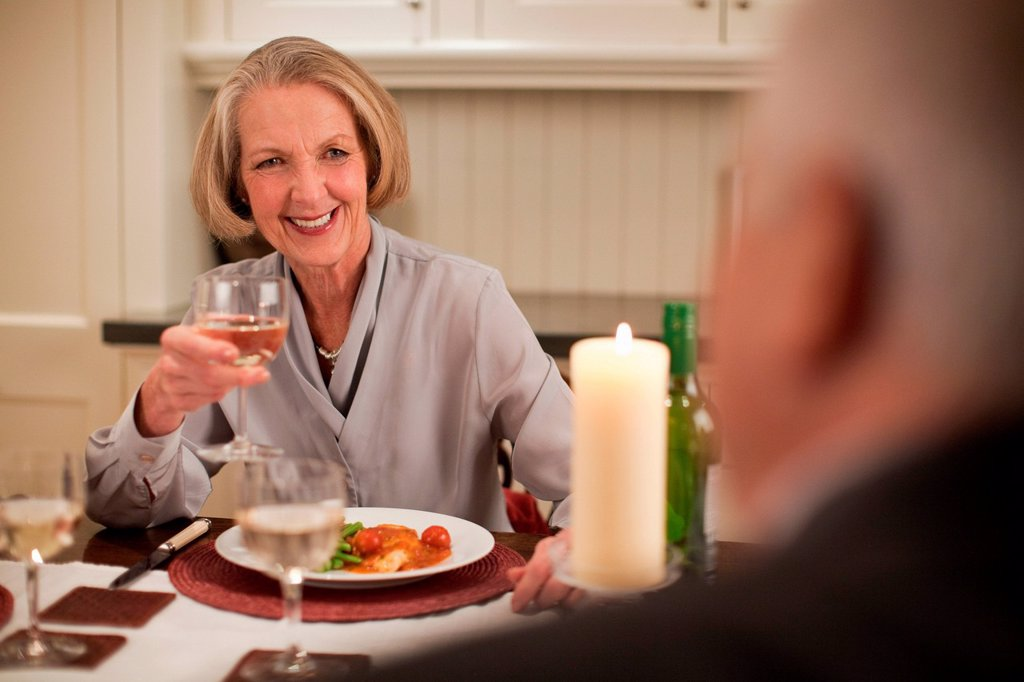 Stock Photo: 1439R-1149668 Senior woman with wine at dinner
