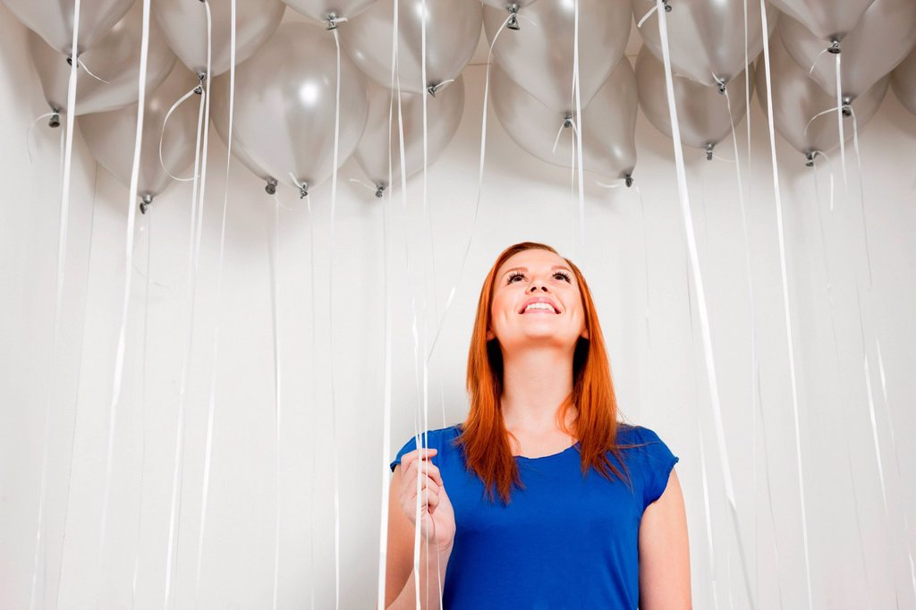 Young woman looking up at balloons : Stock Photo