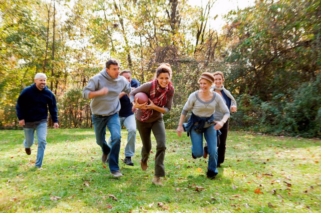 Stock Photo: 1439R-1149855 Mature friends playing football
