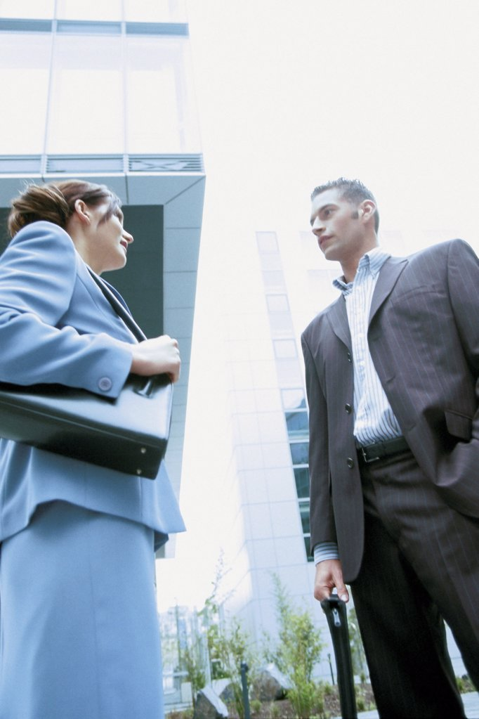 Stock Photo: 1439R-117043 Businessman and businesswoman talking outside office