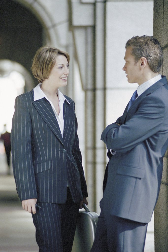 Businessman and businesswoman talking outside office : Stock Photo