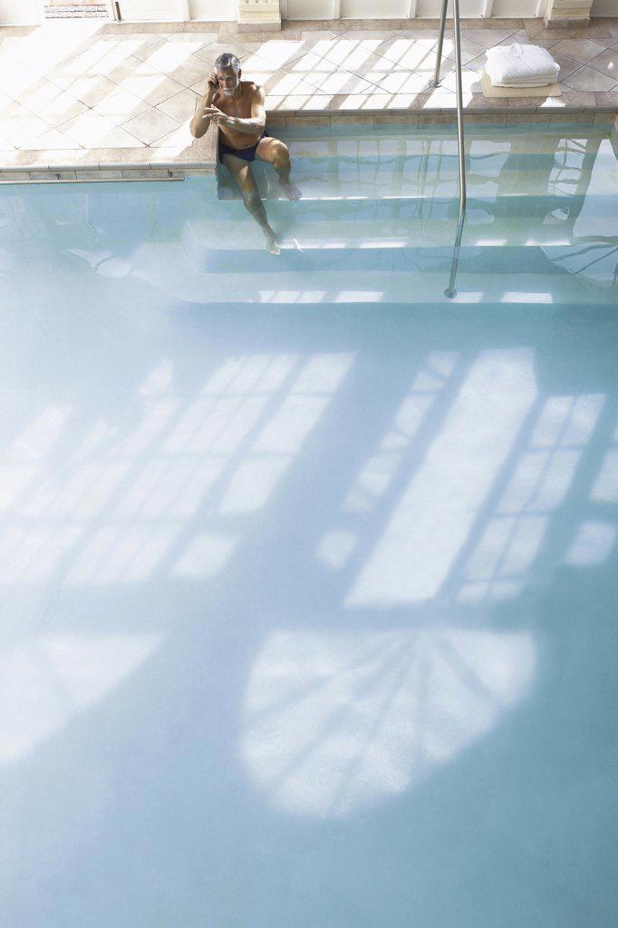 Stock Photo: 1439R-121029 Man on the edge of swimming pool