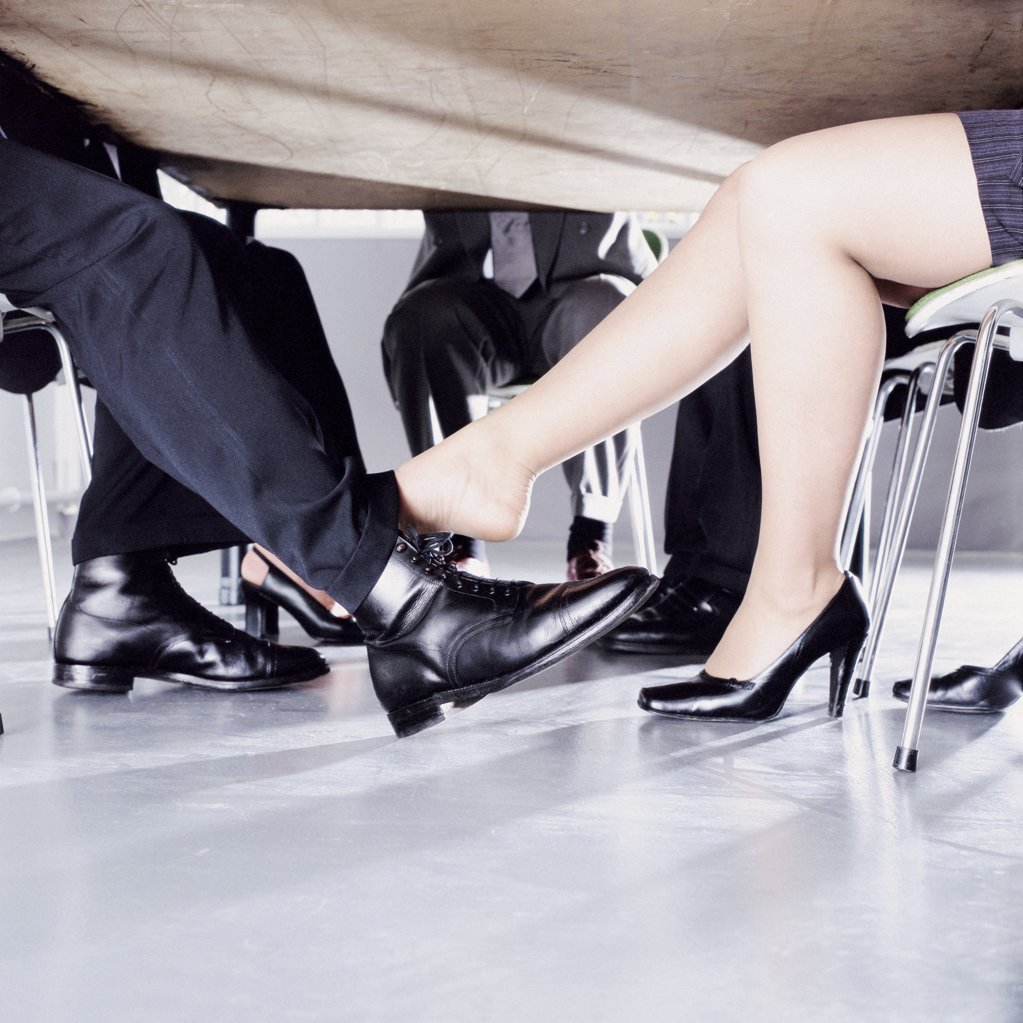 Stock Photo: 1439R-122026 Businesspeople playing footsie