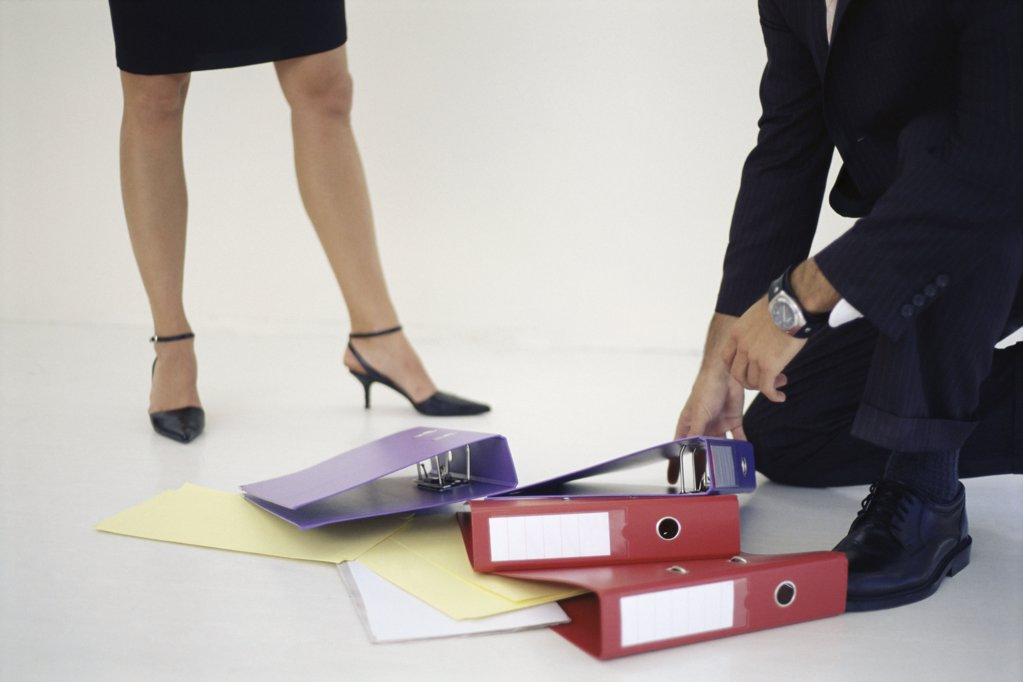 Stock Photo: 1439R-161003 Man picking up folders for woman