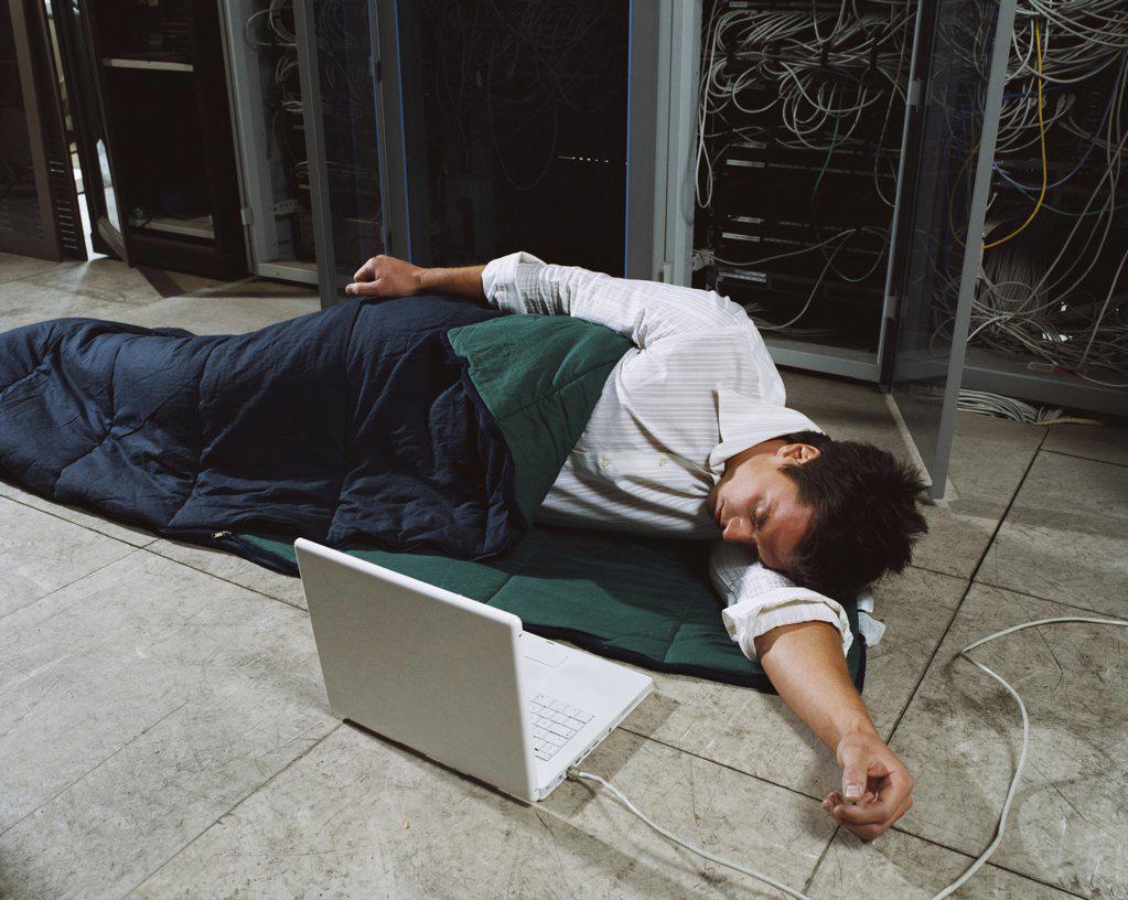 Stock Photo: 1439R-167016 Man sleeping next to laptop