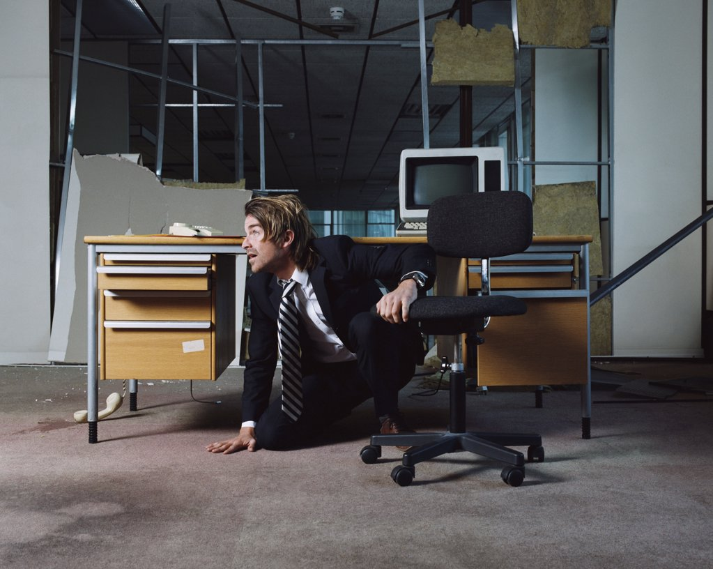 Businessman emerging from under desk : Stock Photo