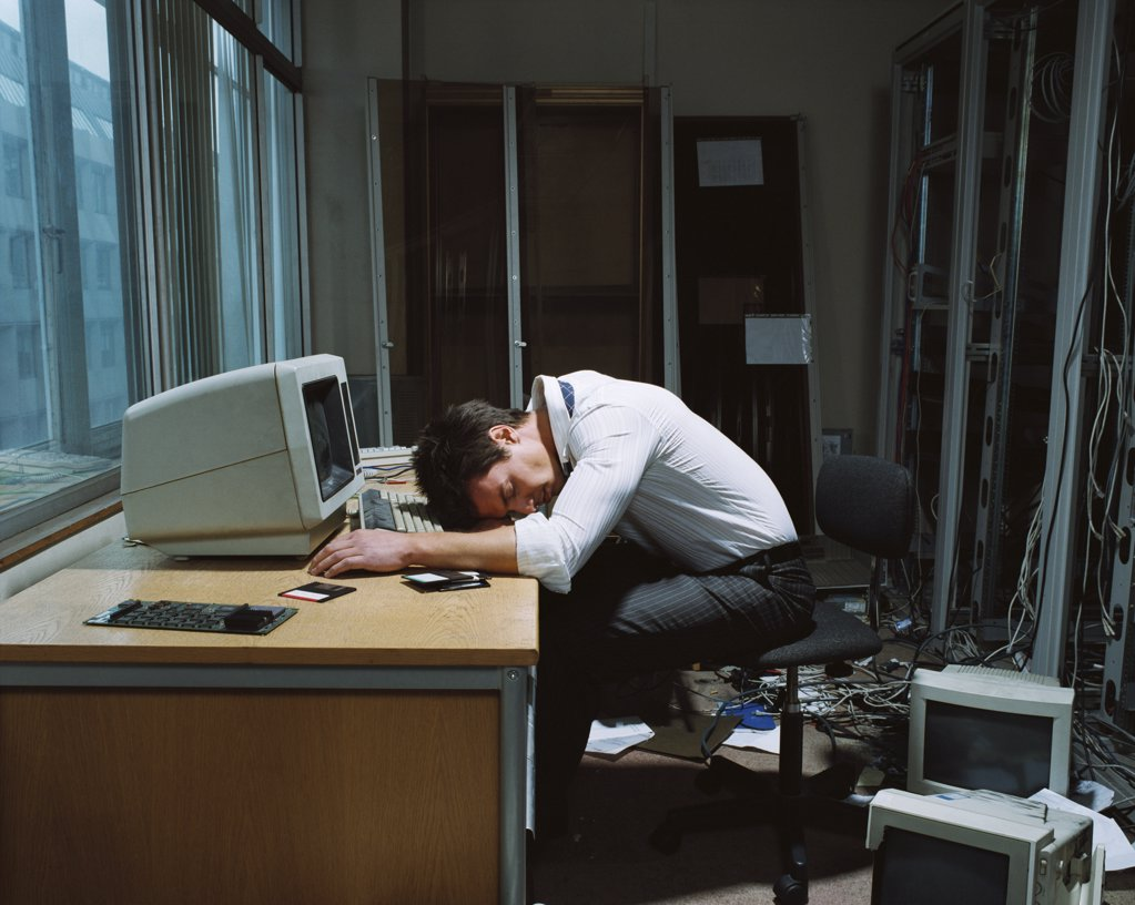 Office worker slumped on his desk : Stock Photo