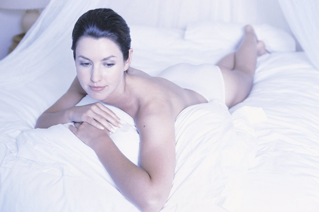 Woman lying on bed : Stock Photo