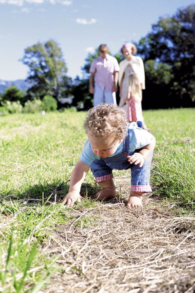 Curious toddler with family in the background : Stock Photo
