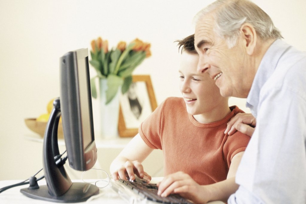 Stock Photo: 1439R-506023 Grandfather and grandson using computer