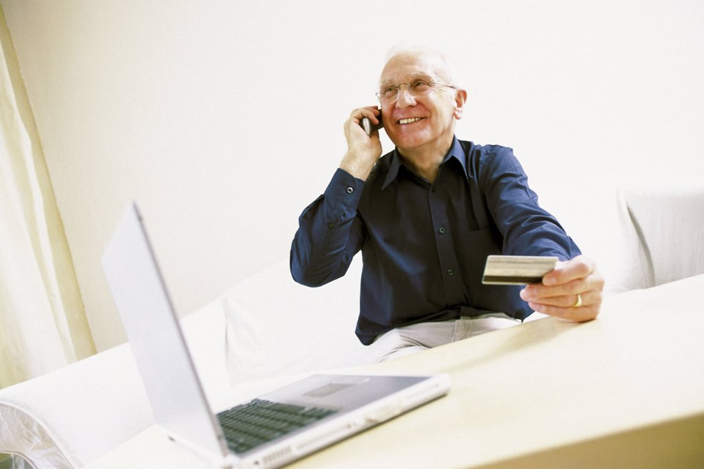 Stock Photo: 1439R-506053 Man using laptop computer and cellphone