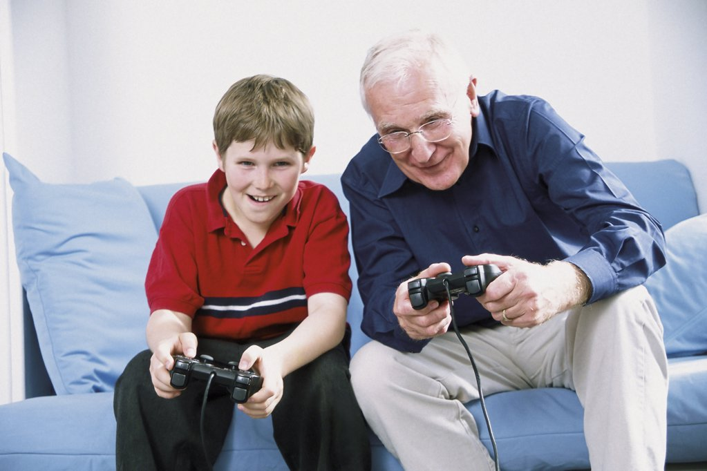Stock Photo: 1439R-506066 Grandfather and grandson playing with computer game