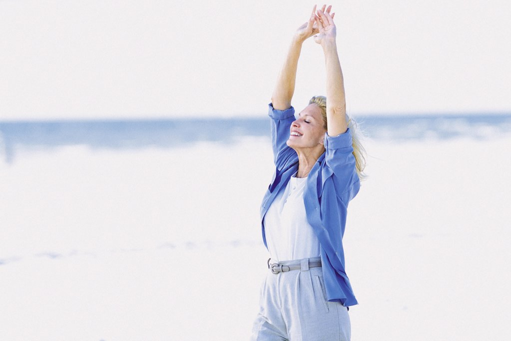 Woman stretching by the sea : Stock Photo