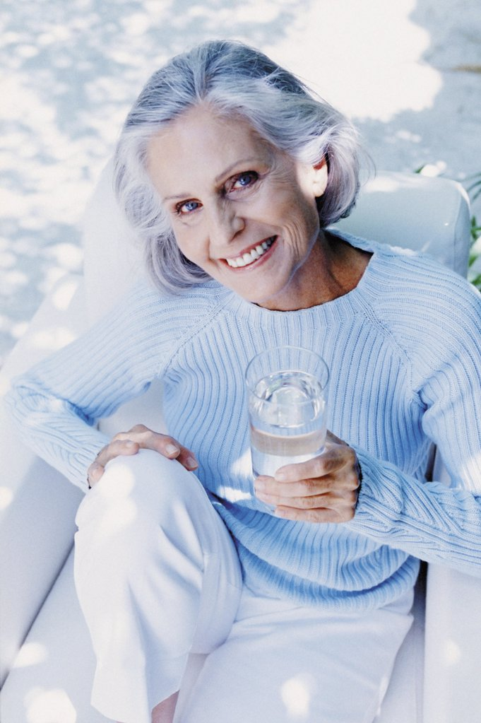 Ageing woman drinking outdoors : Stock Photo